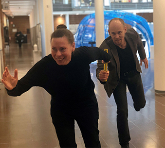 Audio description: Anders Logg handing over the relay baton to Liane Thuvander
