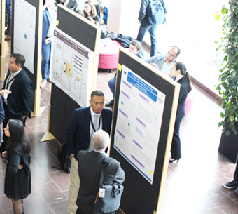 Visual interpretation: Conference visitors seen from above looking at posters.