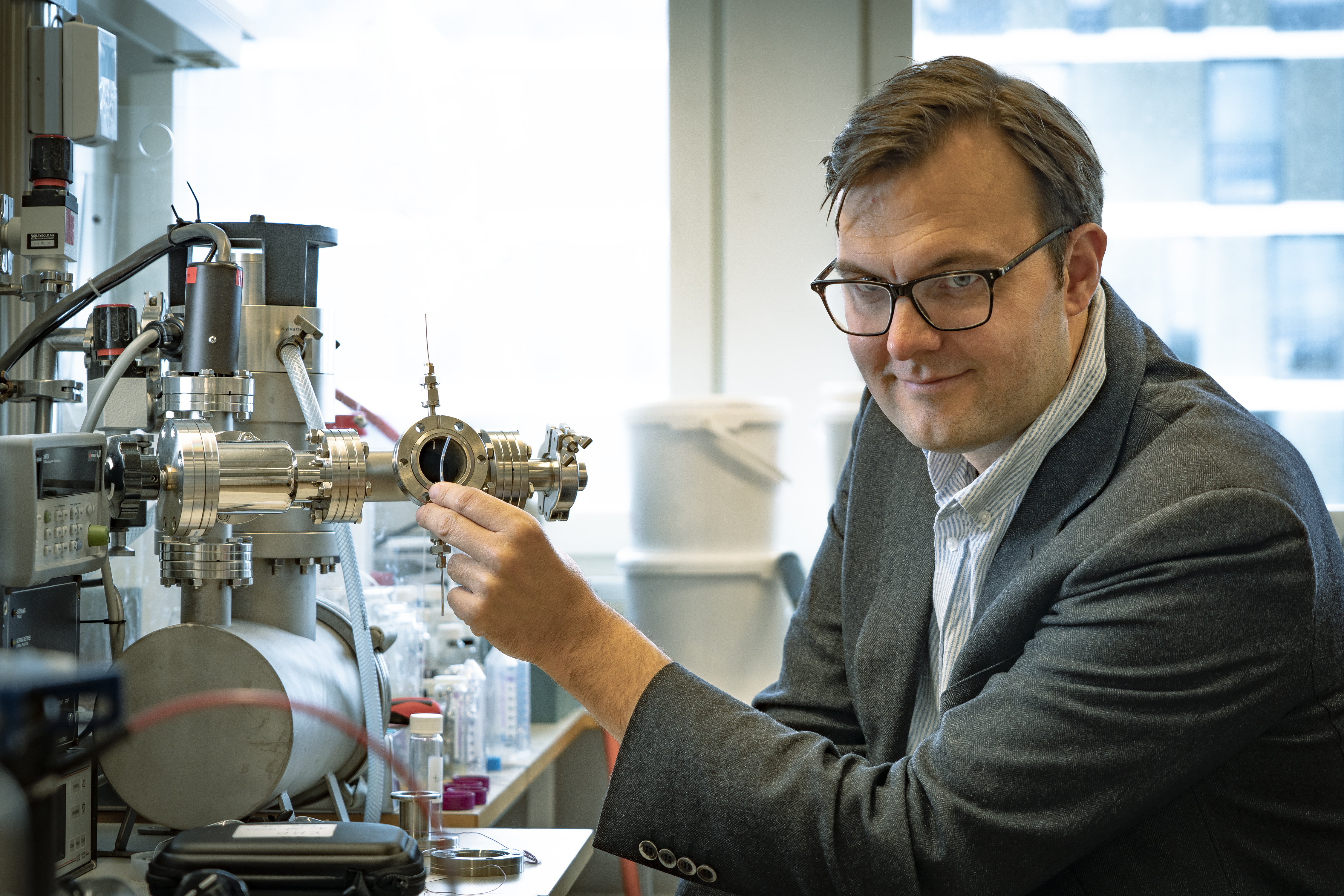 Professor Kasper Moth-Poulsen holding a tube containing the catalyst, in front of the ultra-high vacuum setup that was used to m