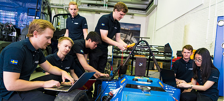 Audio description: Photo of students working on self-driving race car
