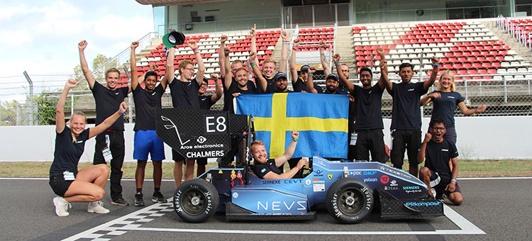 Parts of the team are posing with a swedish flag at the racetrack