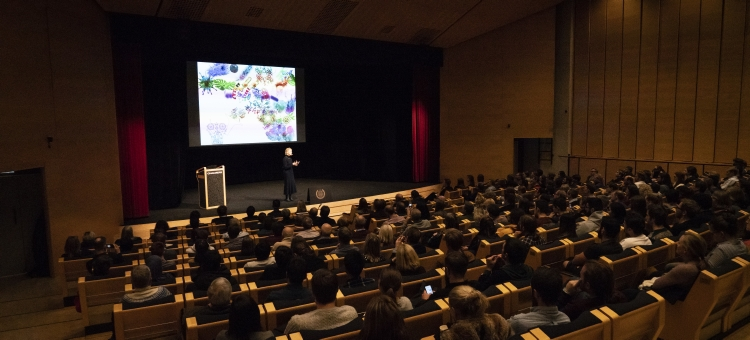 Audio description: Image of Frances Arnold and the audience during the lecture.