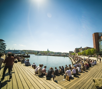 Audio description: Image of people sitting by the water at Chalmers Lindholmen.