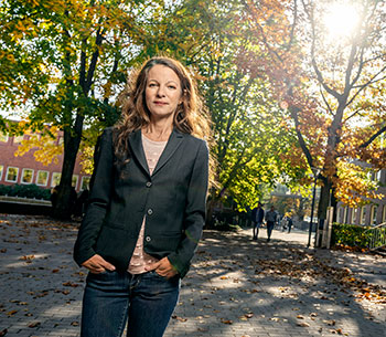 Audio description: Picture of Pernilla Wittung Stafshede, in front of trees and Chalmers buildings.