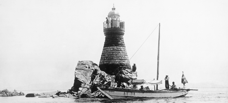 Black and white image of a lighthouse and a boat.