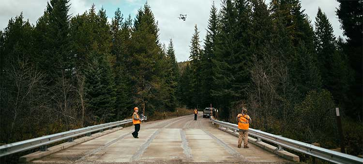 Three road workers with a drone in the air
