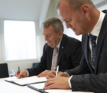 Audio description: Stefan Bengtsson and Mats Fägerhag signing agreement.