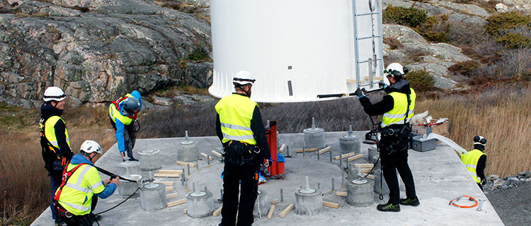 Technicians mounting the wind turbine tower on the concrete foundation.