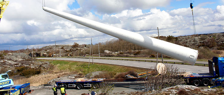 The wind turbine tower is unloaded from the transport with the help of cranes.