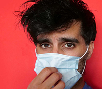 The image is showing a person touching his facemask, which may allow virus and bacteria to spread.