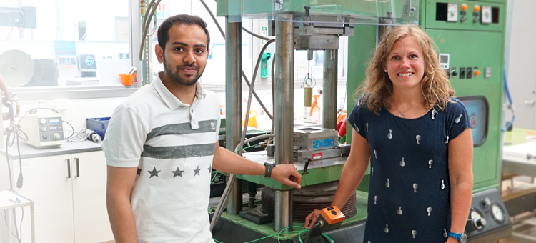 The PhD students in front of a machine